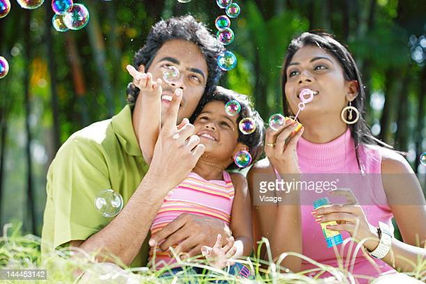 Parents and daughter blowing soap bubbles