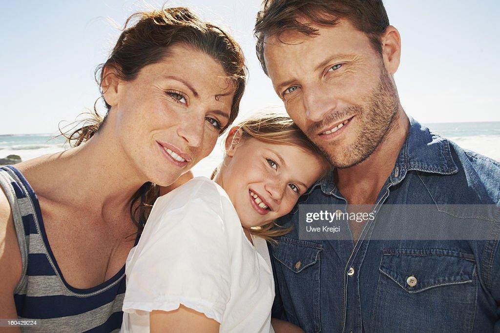 Parents and daughter (6-8) embracing, outdoors : Stock Photo