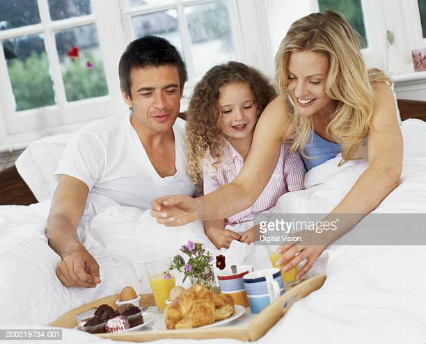 Parents and daughter (4-6)  having breakfast in bed, smiling