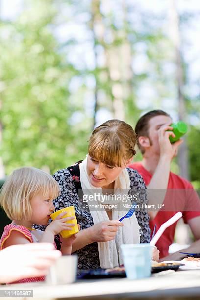 Parents and daughter having picnic at zoo