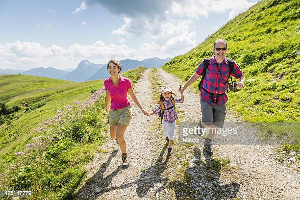 Parents and daughter holding hands on walk, Tyrol, Austria