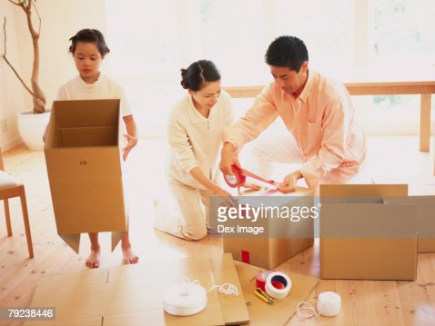Parents and daughter packing boxes : Stock Photo