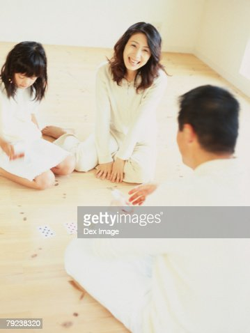 Parents and daughter playing cards : Stock Photo