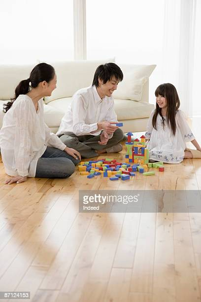 Parents and daughter playing with blocks on floor