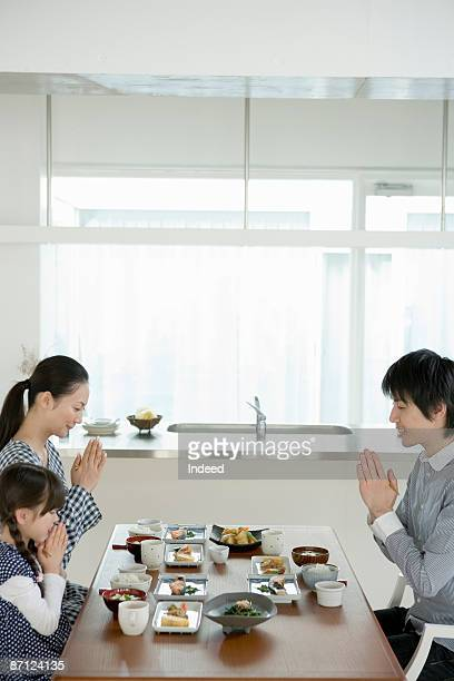 Parents and daughter praying at table