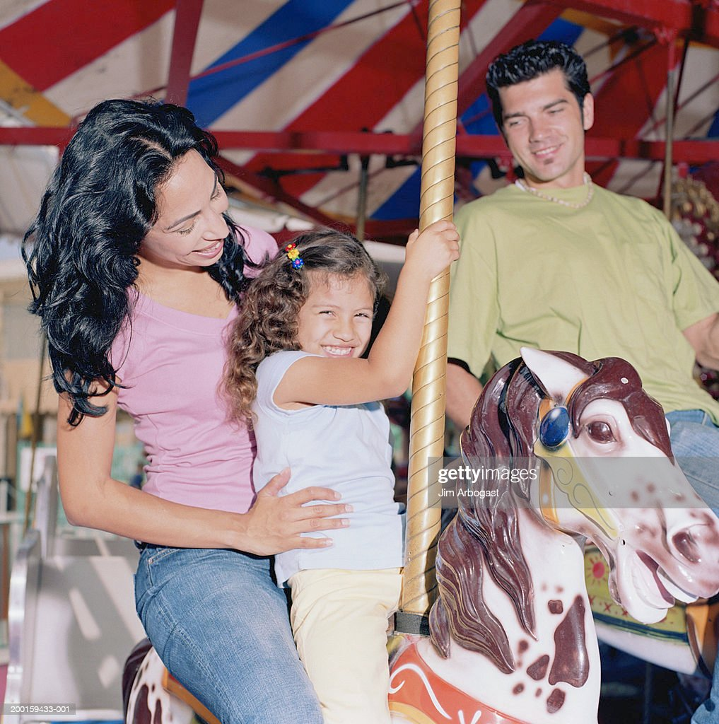 Parents and daughter (3-5) riding on carousel, smiling : Stock Photo