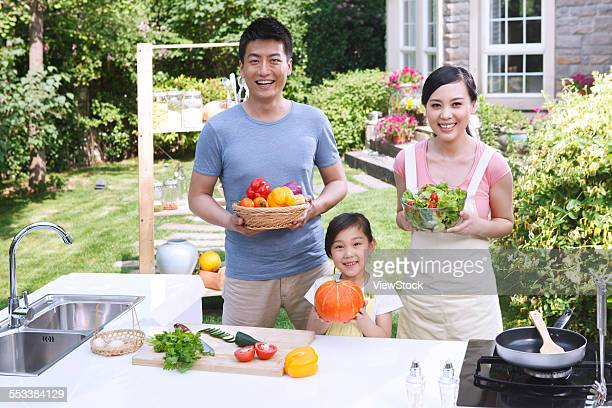 Parents and daughter show fresh vegetables in the outdoor kitchen