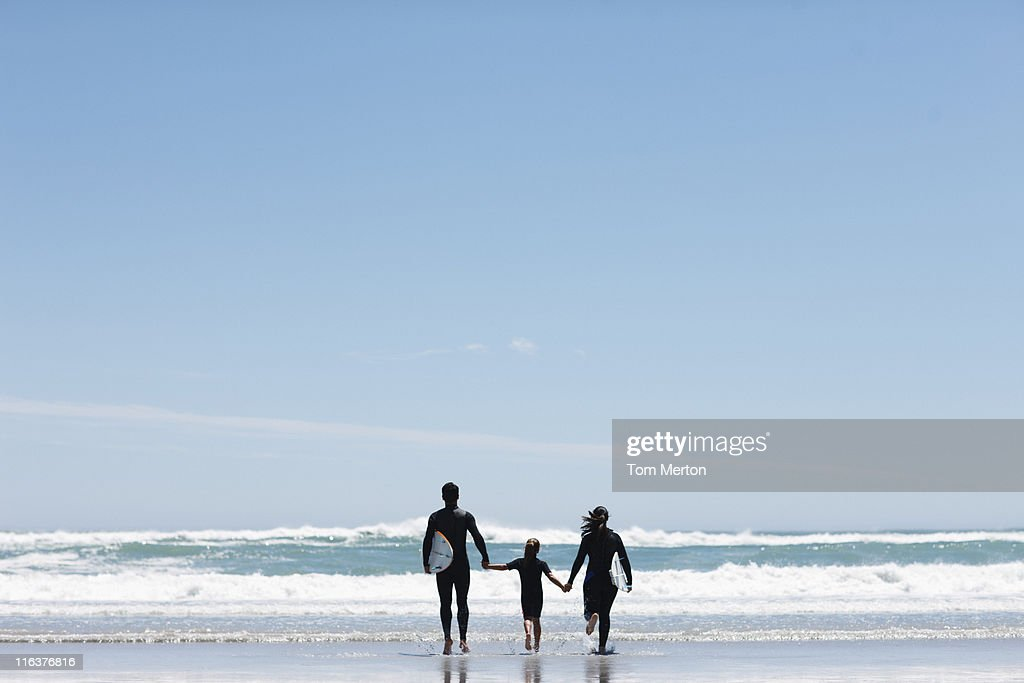 Parents and daughter with surfboard on beach : Stock Photo