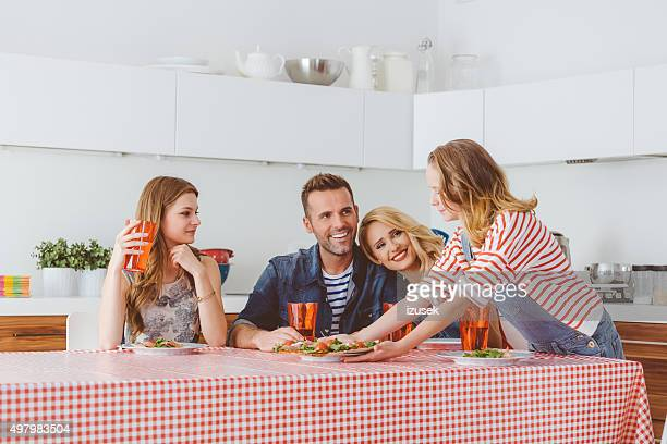 Parents and daughters eating pizza for lunch at home