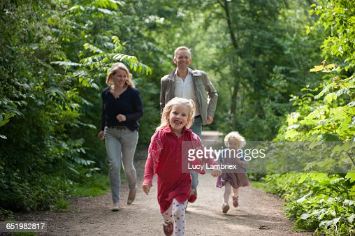 Parents and daughters running : Stockfoto