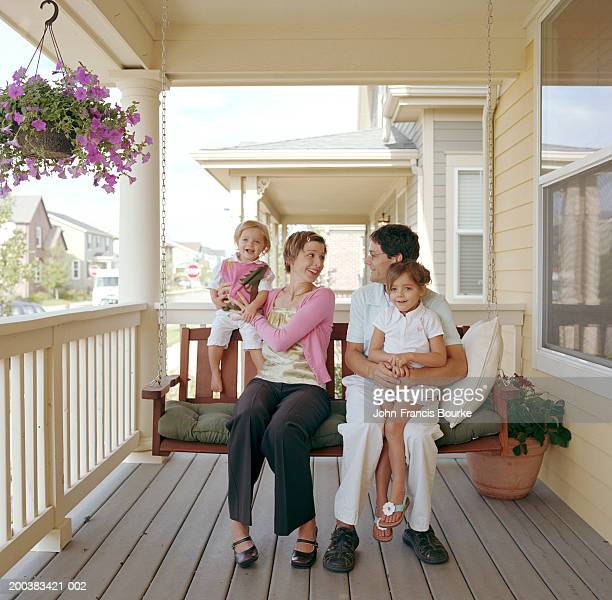 Parents and daughters (21 months to 5) sitting on porch