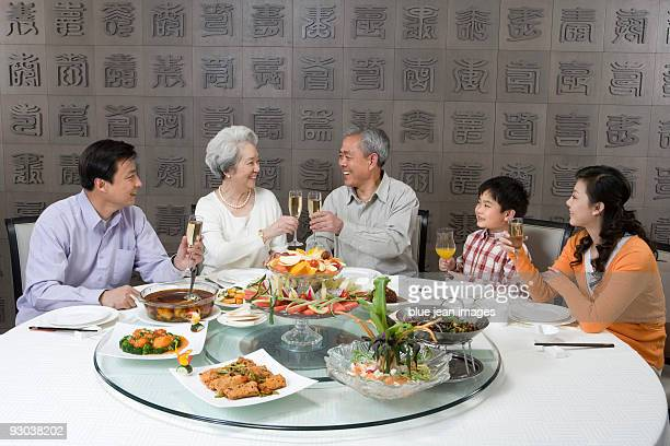 Parents and grandparents with son toasting at dinner table