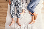 Love makes family. Top view of father, mother and their son in pajamas showing their feet on bed