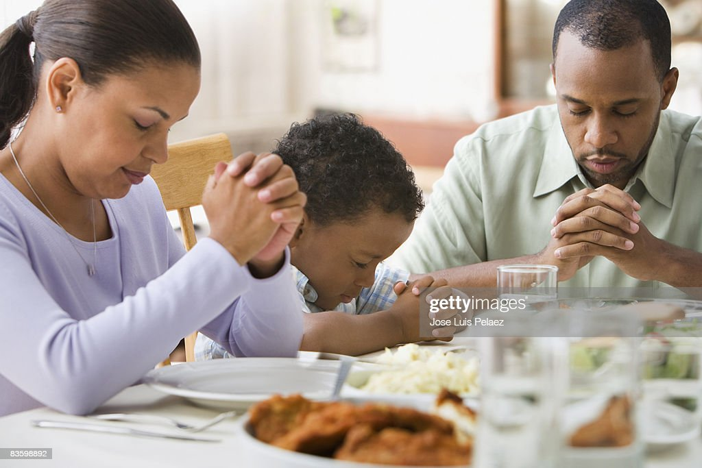 Parents and son giving thanks at the dinner table : Stock Photo