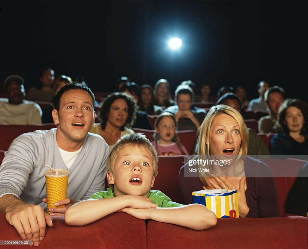 Parents and son (9-11) in cinema reacting to film, close-up