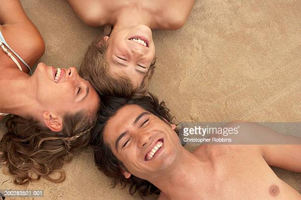 Parents and son lying head to head, eyes closed, smiling, overhead view