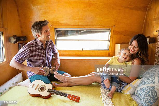 Parents and son on bed in trailer home