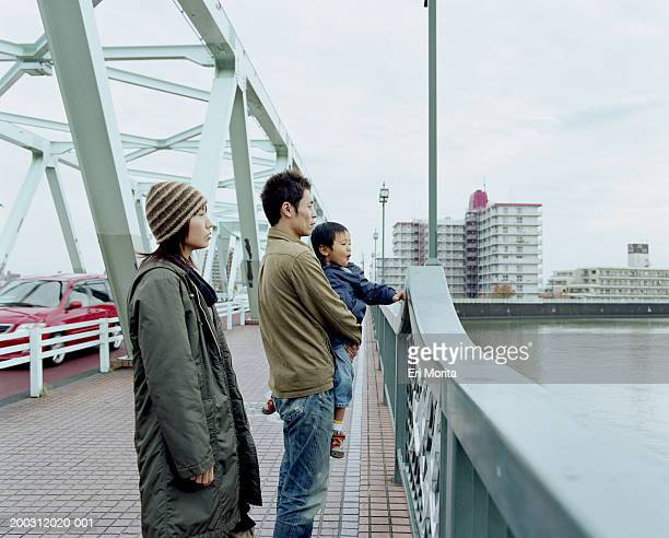 Parents and son (3-5) on bridge looking at water, side view