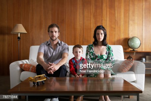 Parents and son (3-5) sitting on couch, in living room