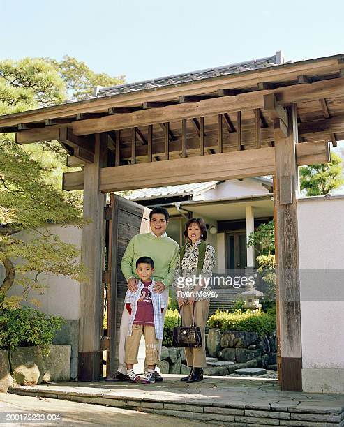 Parents and son (5-7) standing in front of house, smiling, portrait
