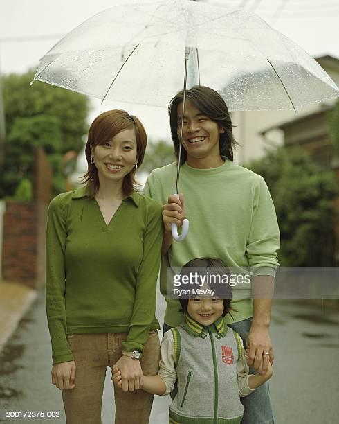 Parents and son (4-6) standing under umbrella, smiling, portrait