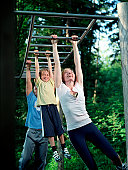 Parents and son (7-9) swinging from bars on exercise course, smiling