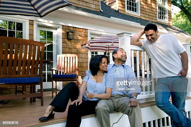 Parents and son talking on back porch