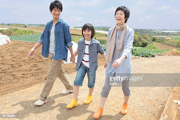 Parents and son walking in field