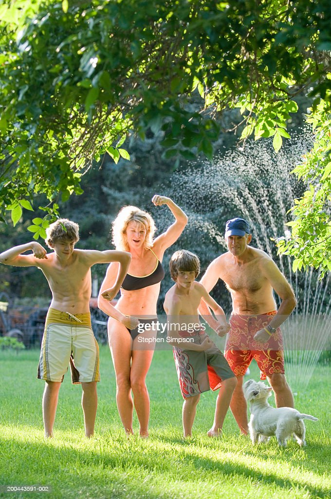 Parents and sons (11-14) playing in sprinkler, summer : Stock Photo