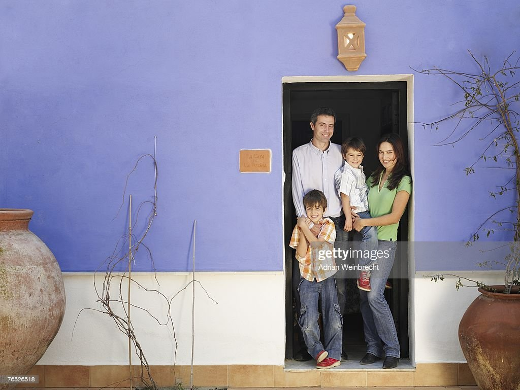 Parents and sons (4-6 years, 5-7 years) standing in doorway, smiling, portrait