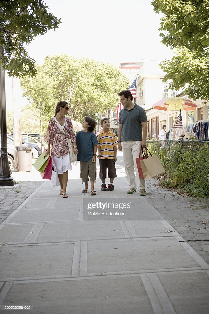 Parents and sons (5-9) walking, parents with shopping bags : Stock Photo