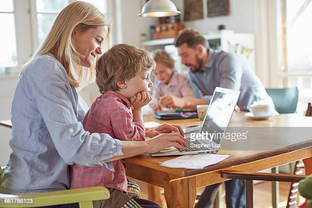 Parents and sons working in home office