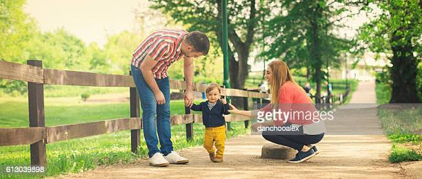 Parents and their baby boy learning to walk