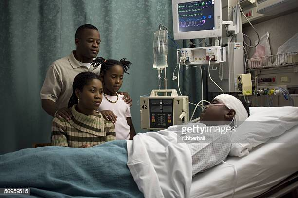 Parents and their daughter looking at a teenage boy in the hospital