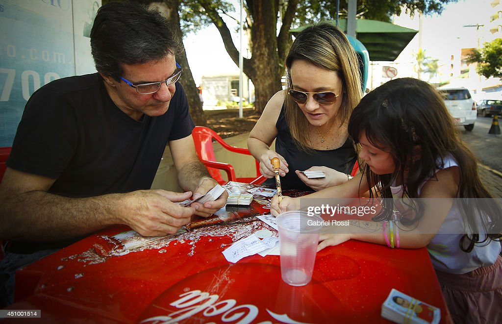Parents and their kids swap Panini 2014 FIFA World Cup Brazil stickers at Praça Popular on June 21, 2014 in Cuiaba, Brazil.