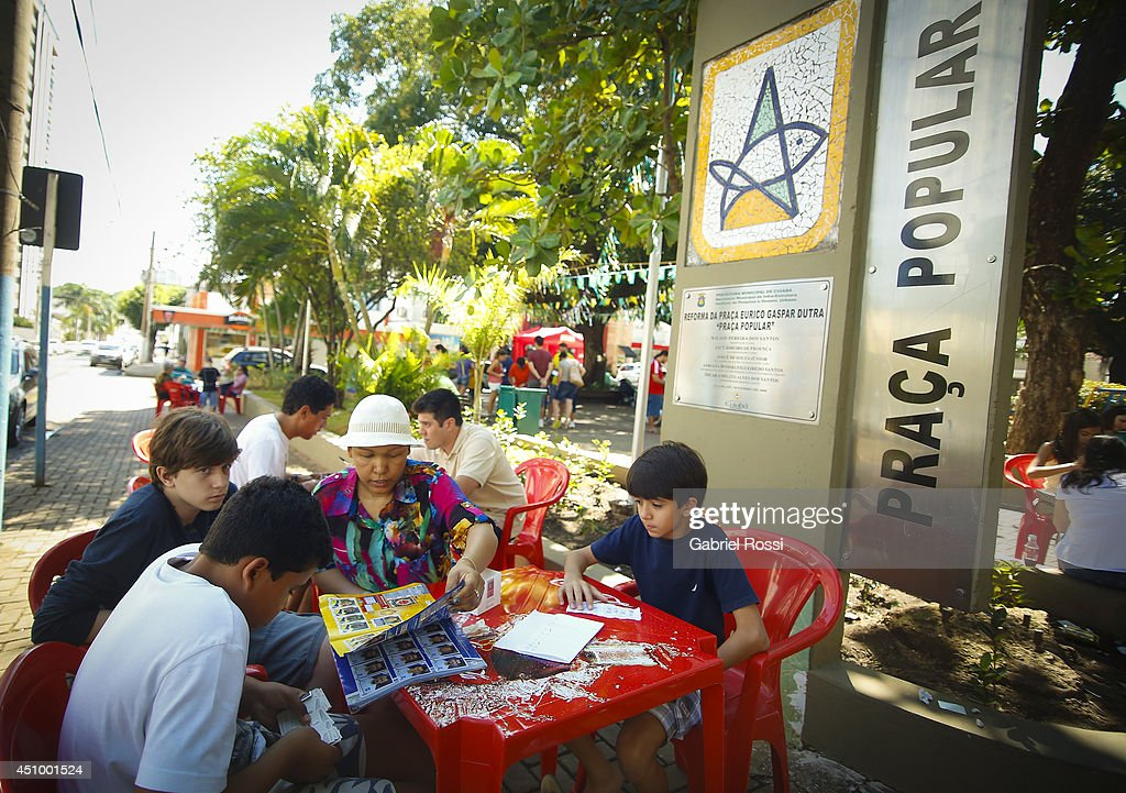Parents and their kids swap Panini 2014 FIFA World Cup Brazil stickers at Praa Popular on June 21, 2014 in Cuiaba, Brazil.