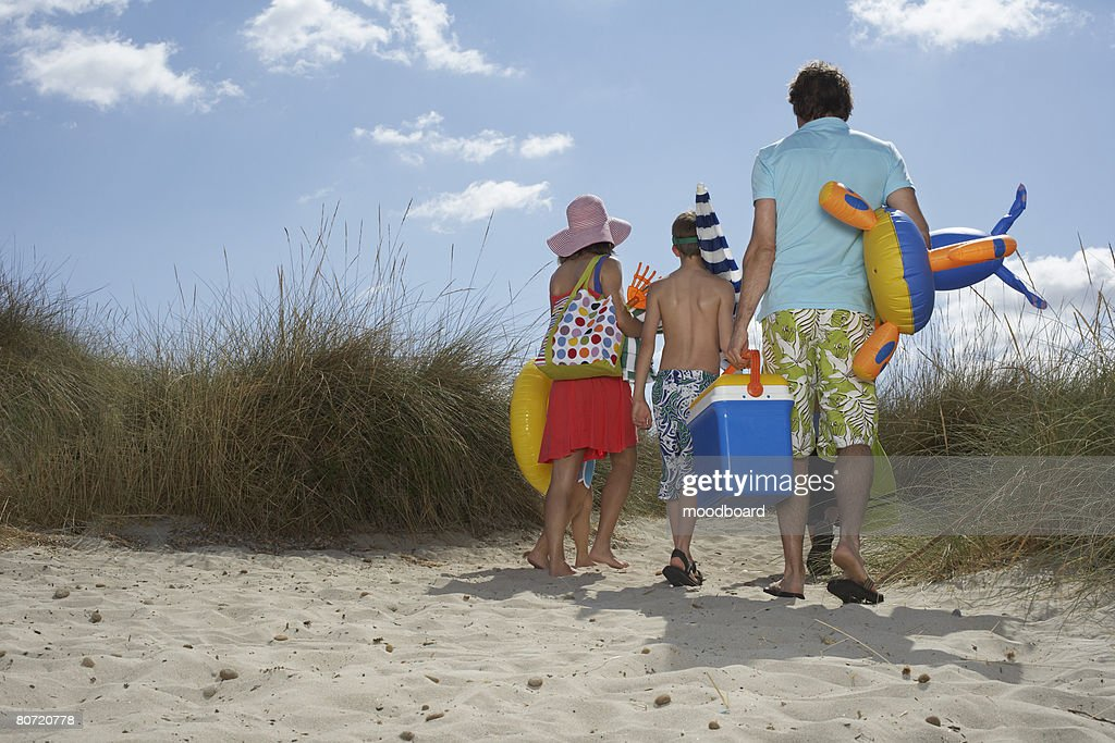 Parents and three children (6-11) carrying beach accessories back view : Stock Photo