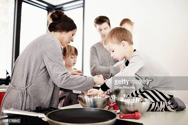 Parents and three children (1-2), (4-5), (6-8) cooking in kitchen