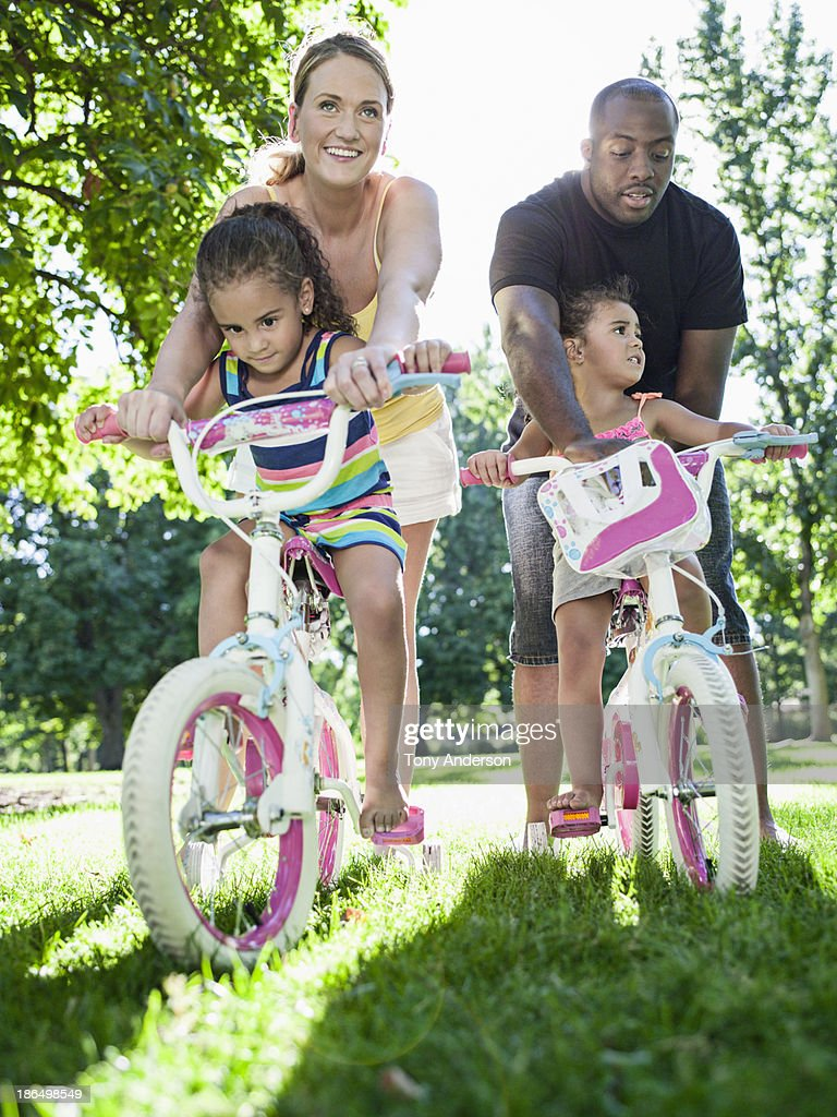 Parents and twin daughters playing on bicycles : Stock Photo