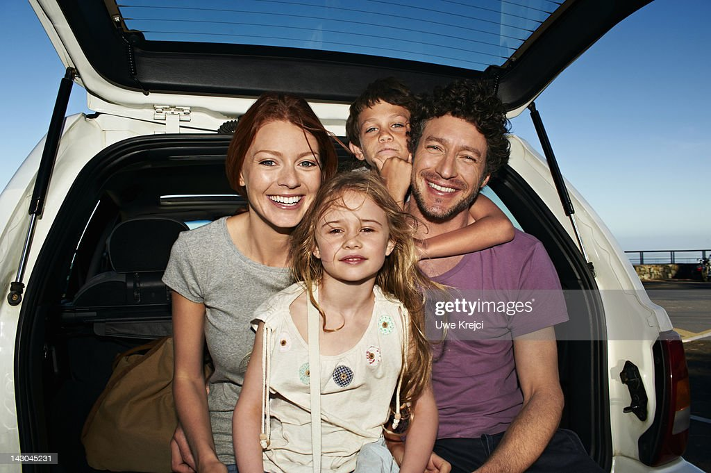 Parents and two children in family car, portrait : Stock Photo