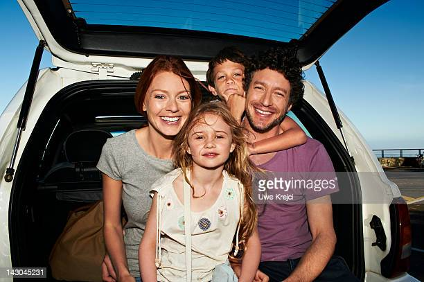 Parents and two children in family car, portrait