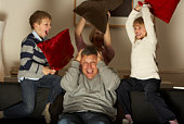 Parents And Two Children In Pillow Fight