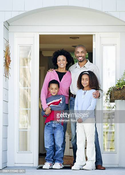 Parents and two children (6-8) standing on front porch, portrait