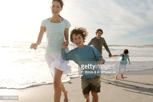 Parents and two children walking on the beach, outdoors : Stock Photo