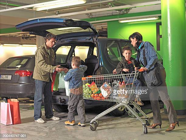 Parents and two sons (4-6) loading shopping into car in car park