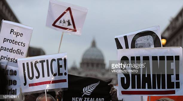 Parents and victims of priest abuse from around the world hold banners reading 'Justice' and 'Shame' during a demonstration in Rome on the background...