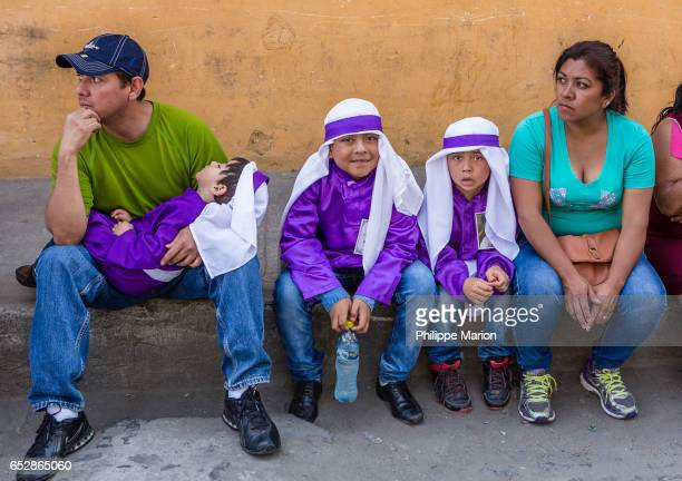 Parents and young boys in traditional clothing during Holy Week in Antigua, Guatemala