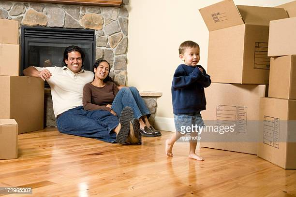 Parents and young child in an empty room with boxes, smiling