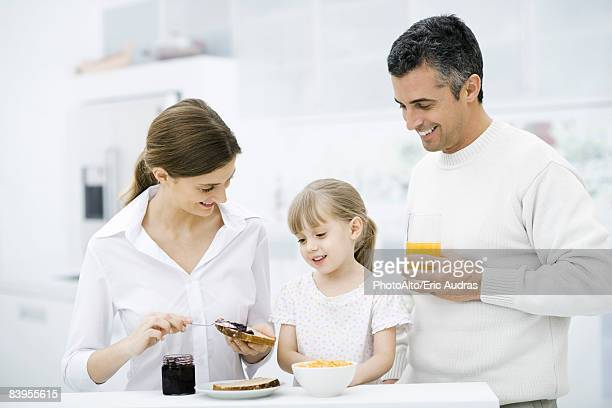 Parents and young daughter preparing breakfast in kitchen