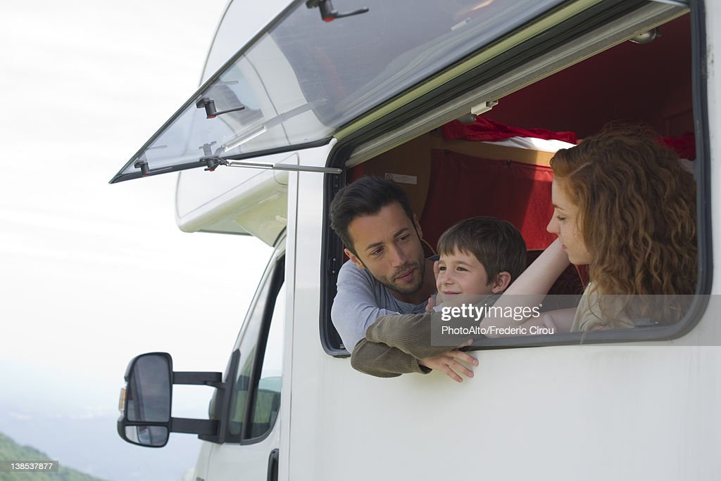 Parents and young son by motor home window